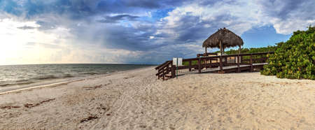 Tiki hut Boardwalk leads down to the white sand of Barefoot Beach in Bonita Springs, Florida