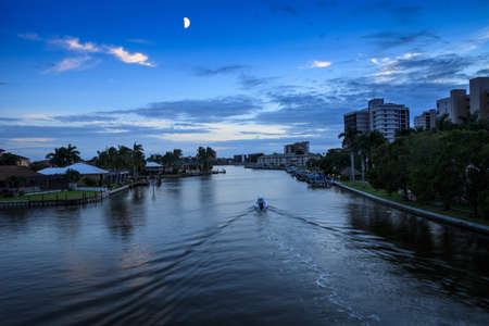 Boat returns to dock at dusk as the moon comes up over Wiggins Pass in Naples, Florida. Stockfoto