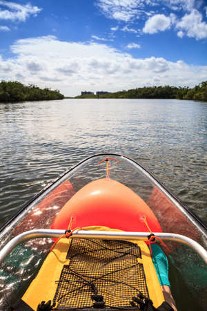 Yellow, waterproof backpack inside a Clear see-through kayak forges its way through the waters of Delnor-Wiggins pass in Bonita Springs, Florida. Stockfoto