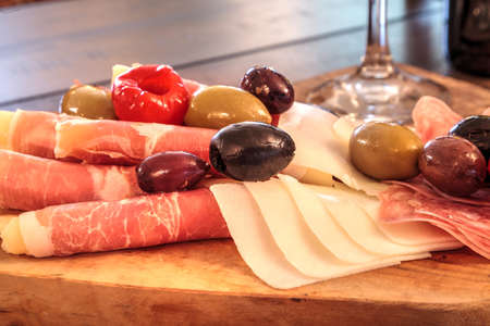 Charcuterie board on rustic wood with candles behind a spread of prosciutto panino, mozzarella cheese, Genoa salami, Fontina cheese and artisanal crackers.