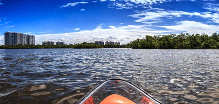 Clear see-through kayak forges its way through the waters of Delnor-Wiggins pass in Bonita Springs, Florida.