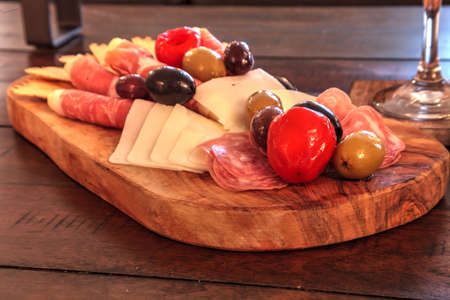 Charcuterie board on rustic wood with candles behind a spread of prosciutto, mozzarella cheese, Genoa salami, Fontina cheese and artisanal crackers.
