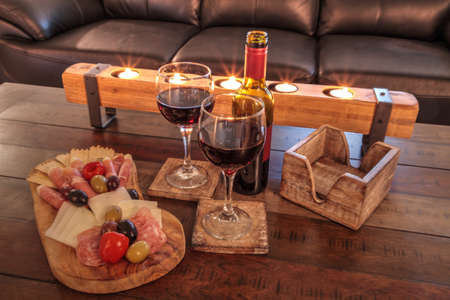Red wine with Charcuterie board on rustic wood with candles behind a spread of prosciutto panino, mozzarella cheese, Genoa salami, Fontina cheese and artisanal crackers. Stockfoto