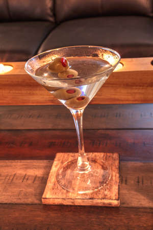 Dirty martini with green Pimento olive on a rustic wood coaster with rustic candles behind.