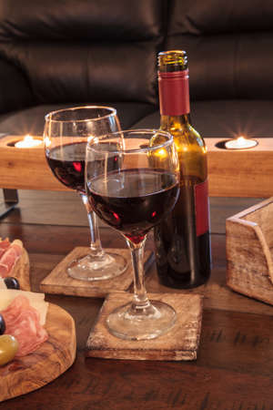 Dark red wine on a rustic wood coaster with rustic candles behind.