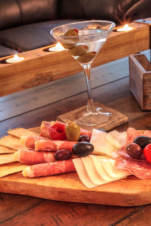 Martini with olives and a Charcuterie board on rustic wood with candles behind a spread of prosciutto panino, mozzarella cheese, Genoa salami, Fontina cheese and artisanal crackers. Stockfoto