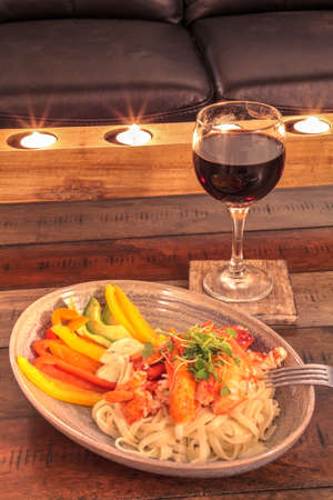 Red wine with Maine lobster over a bed of linguini with micro greens, colorful peppers and avocado sauce.