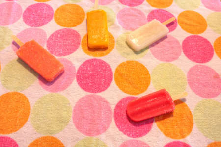 Fruit ice cream stick on a dotted background in summer including watermelon  ice cream stick , tropical fruit  ice cream stick , mango  ice cream stick , and lime  ice cream stick with fresh raspberries.