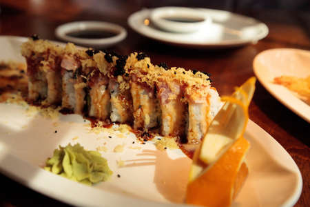 Crispy tuna sushi roll with tempura in the center with rice and masago fish roe eggs with wasabi on the side. Stockfoto