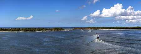 Boats sail through New Pass of Estero Bay toward the ocean and Lovers Key State Park on the edge of Bonita Springs and Fort Myers, Florida.
