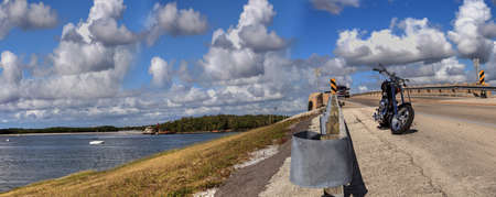 Bonita Beach, Florida, USA – November 16, 2020: Motorcycle along the side of a highway bridge of Bonita Beach causeway over Estero Bay in Bonita Springs, Florida. Redactioneel