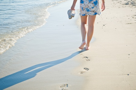 Lady walking barefoot on the sand beach.