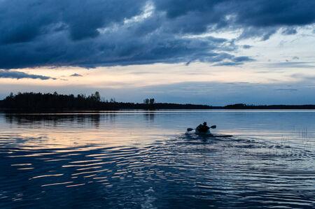 kayaker: Summer sunset kayaking at Vuoksa lake. Lonely kayaker.