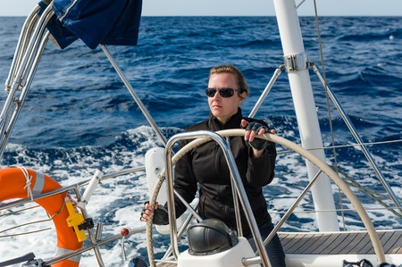 Woman captain at the helm of big cruising yacht