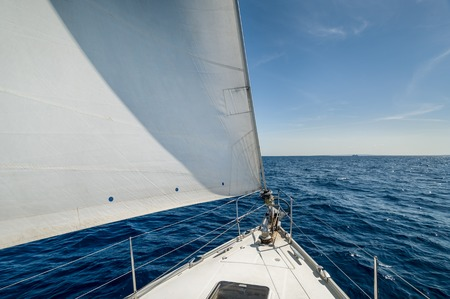Cruising yacht bow with hoisted sails. Balearic islands, Spain