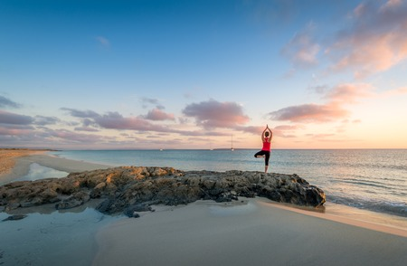 Girl doing yoga at Formentera beach. Wonderful sunrise scene. Standard-Bild