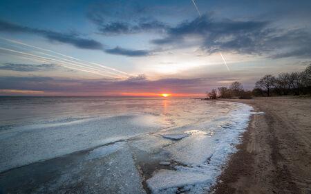 leningradskaya: Sunset at frozen bay. Ice on the water and sand beach line