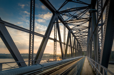 steel arch bridge: Inside view of big steel railway bridge on sunrise. Savonlinna, Finland Stock Photo