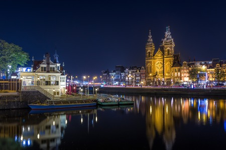 Night long exposure photo of St. Nicholas church and Amsterdam channels. photo