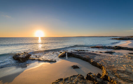 sea in the horizon: Sun is rising at the horizon and lit sand beaches of Formentera island. Spain.