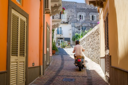lipari: Man riding scooter on the narrow streets of Italy