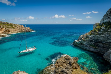 bay: Dream bay seascape with turquoise transparent water and sailing boat. Mallorca island, Spain Stock Photo