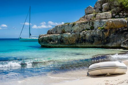 Dinghy at perfect sand beach and sailing yacht at the horizon. Baleares, Spain