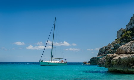 Sailing yacht at the horizon. Cala Marmolis, Mallorca island, Spain Standard-Bild