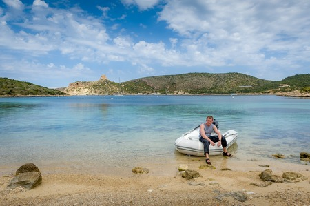 pirate crew: Sailor sits in inflatable raft of sailboat at paradise bay of Cabrera island. Spain. Stock Photo