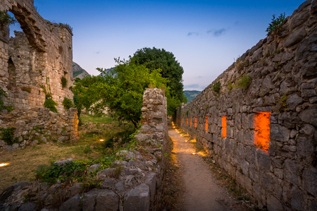 stary: Old Bar fortress walls night lightning in the windows. Montenegro. Stock Photo
