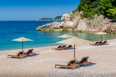 budva: Adriatic sea paradise bay between rocks and mountains. Wooden chaise-longue chairs and umbrellas. Montenegro. Stock Photo