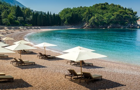 budva: Adriatic sea sand beach at beautiful small bay near the famous Sveti Stefan historical island. Montenegro.