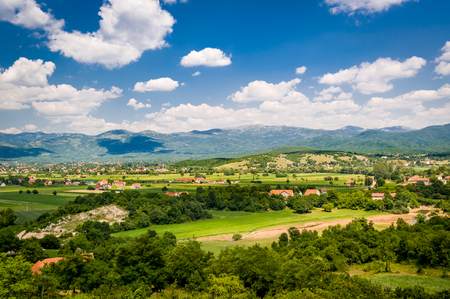 Typical Montenegrin rural landscape. Village houses in the fields, small river and mountain range on a background. Niksic, Montenegro. Standard-Bild