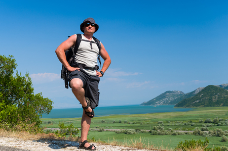 blinders: Happy tourist in sun hat with his backpack stands on a background of Skadar lake national park landscape. Hot summer day near Virpazar, Montenegro.
