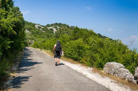 blinders: Tourist with backpack is going up the hill in the Skadar national park. Montenegro hiking routes.