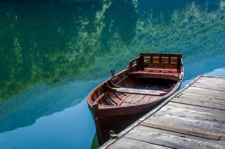 mirror on the water: Traditional wooden boat, sky and forest reflected in the mirror water of the Biogradsko lake. National park Biogradska gora, Montenegro.