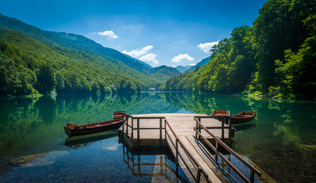 touristic: Panoramic view of Biogradsko lake. Virgin forests and beautiful mountains, wooden pier and boats. National park Biogradska gora is very popular touristic destination in Montenegro.