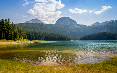 national forests: Black Lake waters, mountains peaks and forests at Durmitor national park landscape. Montenegro. Stock Photo