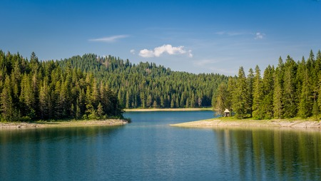 national forests: Small wooden house at the mountain lake shore. Thick coniferous forests at Black Lake, national park Durmitor, Montenegro Stock Photo
