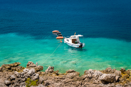 tourquoise: Small fishing boat moored at paradise bay. Stone shores and beautiful turquoise water. Montenegro.