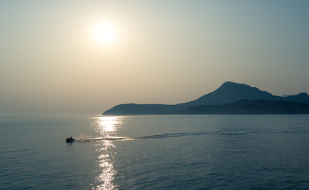jetski: Jetski going fast in the calm sea with mountain range silhouettes at the background. Evening against the sun photo. Montenegro. Stock Photo
