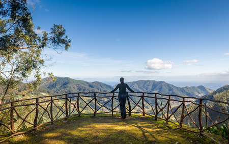 Woman looking at mountain landscape from Santo da Serra park viewpoint. Madeira island, Portugal. Standard-Bild