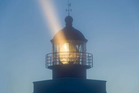strong light: Strong light beam from old lighthouse tower in the fog. Night in Ponta do Pargo, Madeira island. Stock Photo