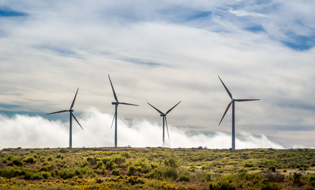windpower: Four big wind generators in the mountain field over the clouds. Madeira island, ER105 road, Portugal.