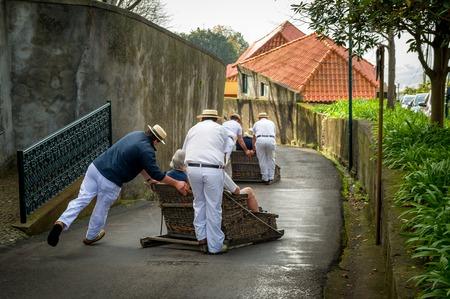 Funchal의 거리에서 전통적인 지팡이 썰매를 내리막 길에 내딛는 Toboggan의 라이더. 몬테 공원, 마데이라 섬, 포르투갈 스톡 콘텐츠