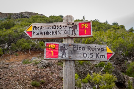 steep cliff sign: Wooden road sigh pointing to Pico Arieiro and Pico Ruivo at the highest walking path of Madeira island.