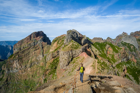 Woman hiker on the dangerous path between the rocky cliffs of Pico Arieiro hiking path. Madeira island, Portugal.