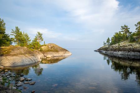 mirror on the water: Beautiful mirror water and stone shores of Karelia islands. Ladoga lake, Russia. Stock Photo