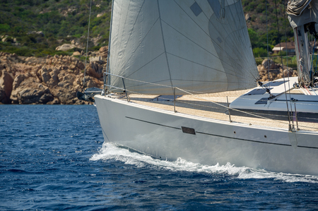 cruising: Luxury new cruising sailboat bow with teak deck under hoisted sails and some heeling, bow view from port side. Sardinia, Italy. Stock Photo