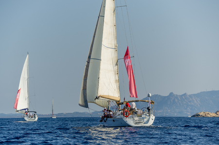 cruising: Group of sailboats under the hoisted sails in the Mediterranean. Sardinia, Italy.